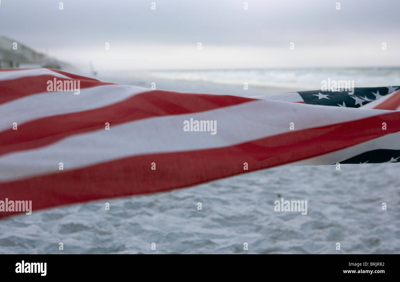 An American flag is blowing in the foreground with the beach and ocean in the background. - Stock Image