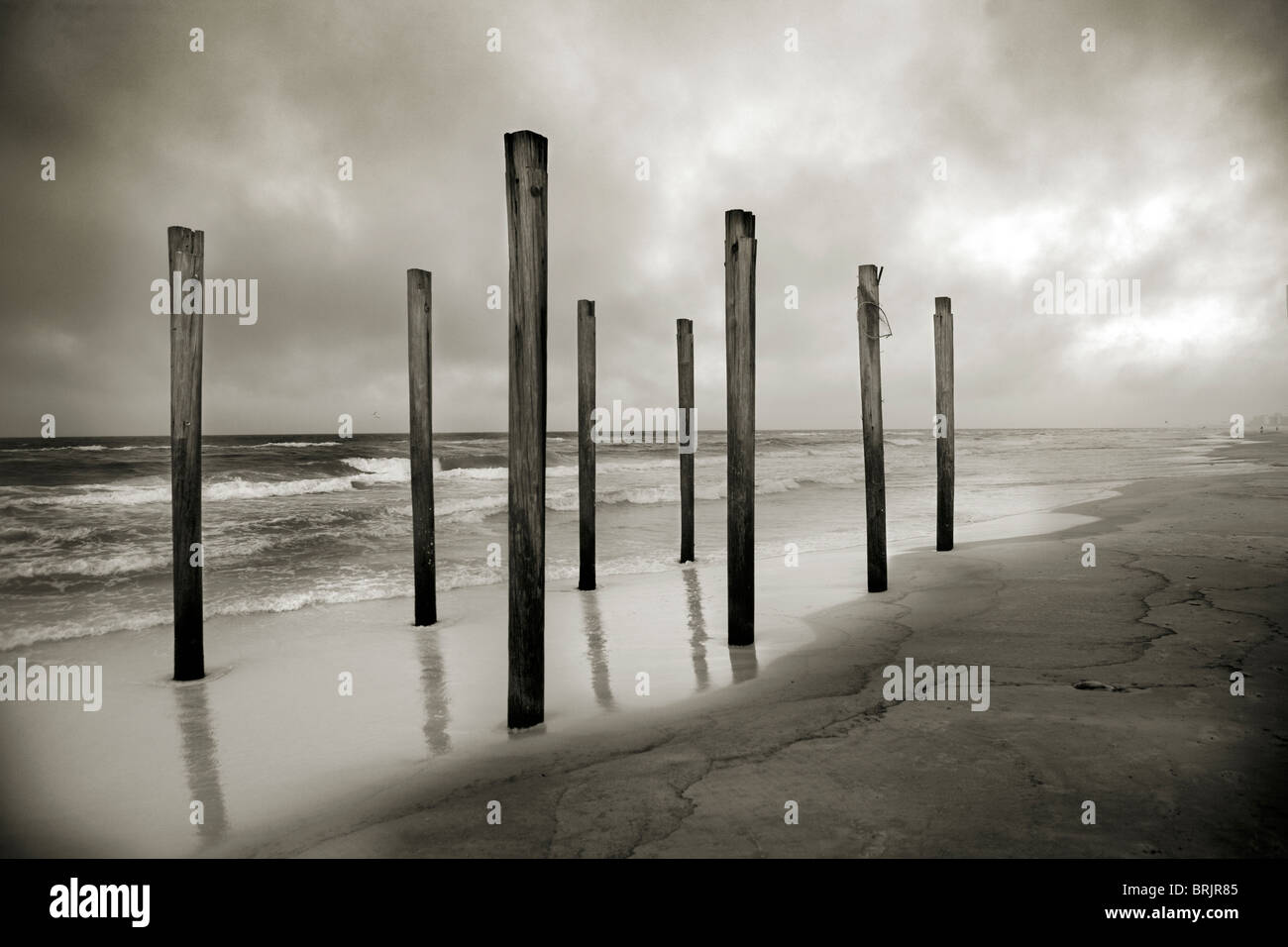A sepia toned shot of old beach posts at the shoreline with clouds and ocean in the background. - Stock Image