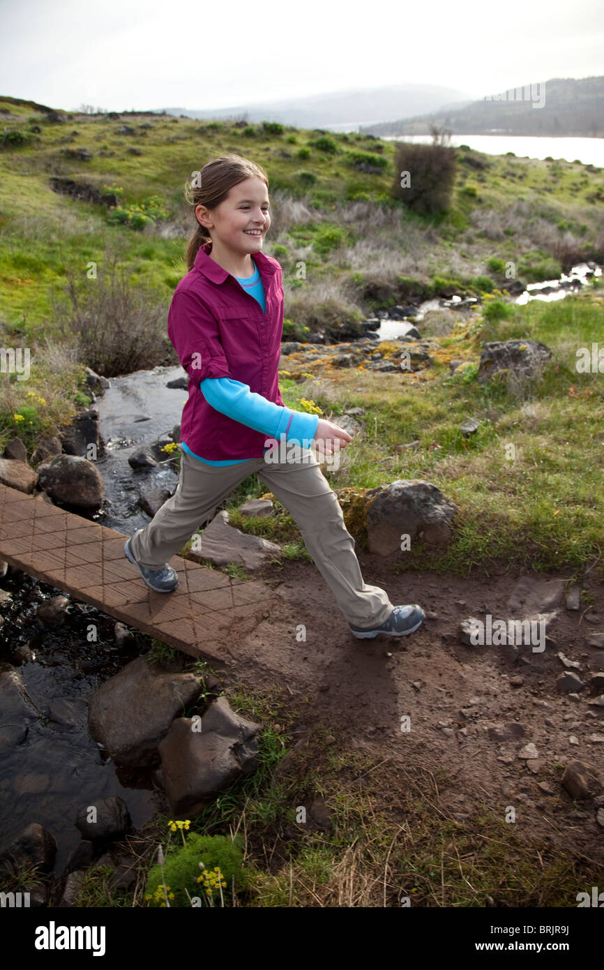 A young girl hiking on a sunny spring morning. - Stock Image