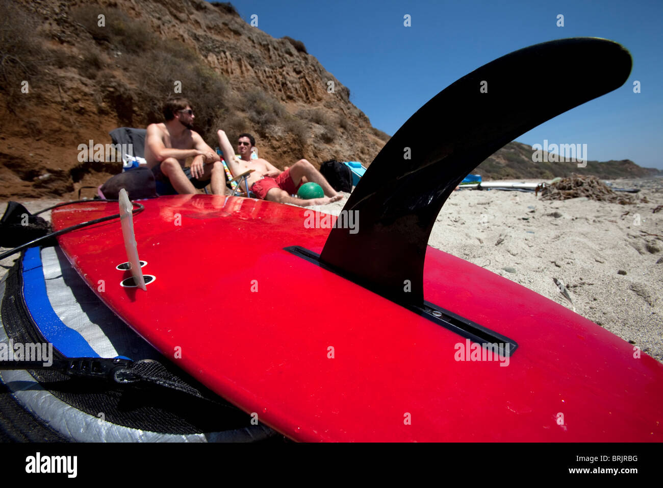 Two men lounging on the beach with a surfboard prominent in the foreground. - Stock Image