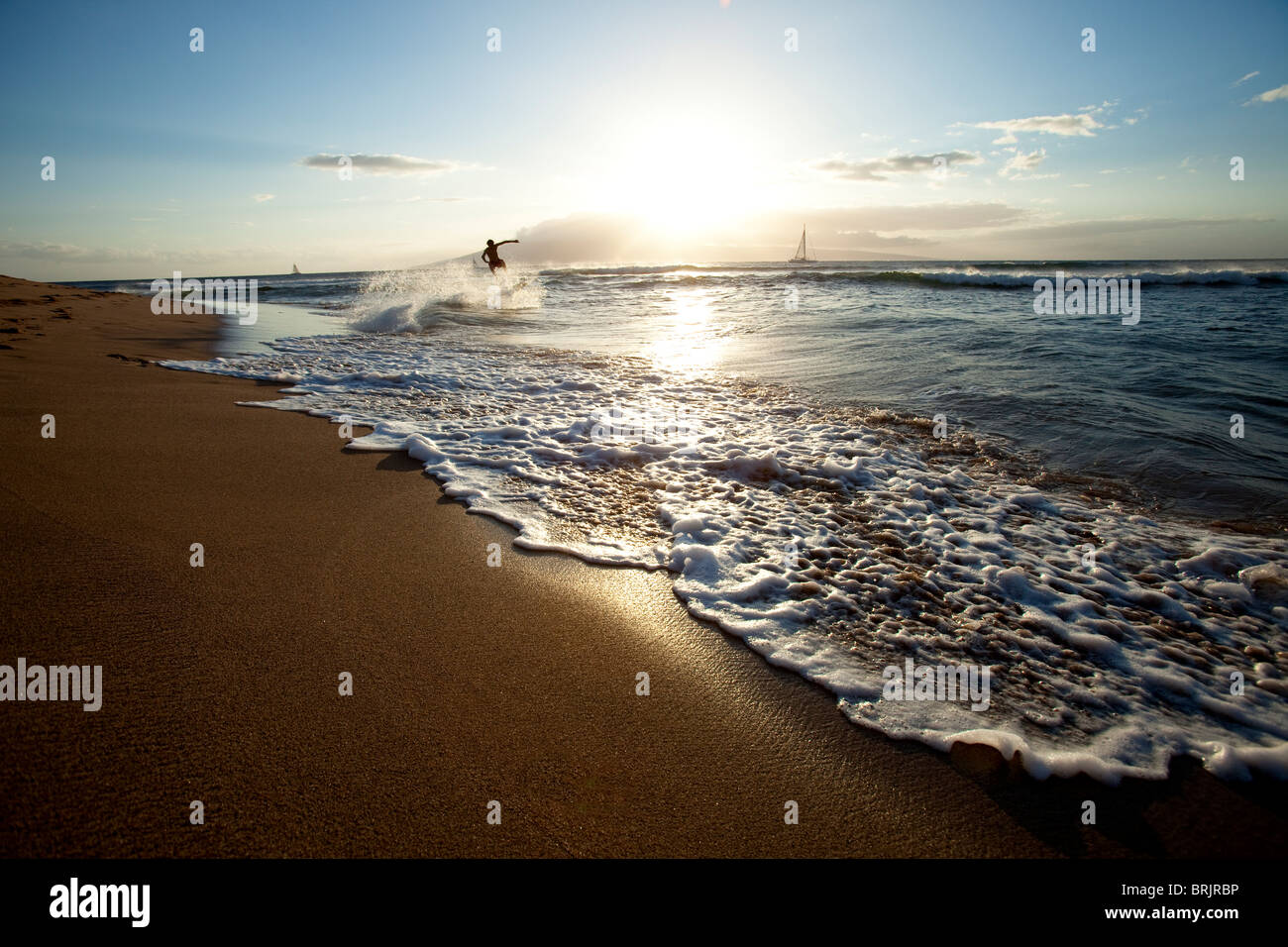 One man skimboarding at sunset with sailboats in the background. - Stock Image
