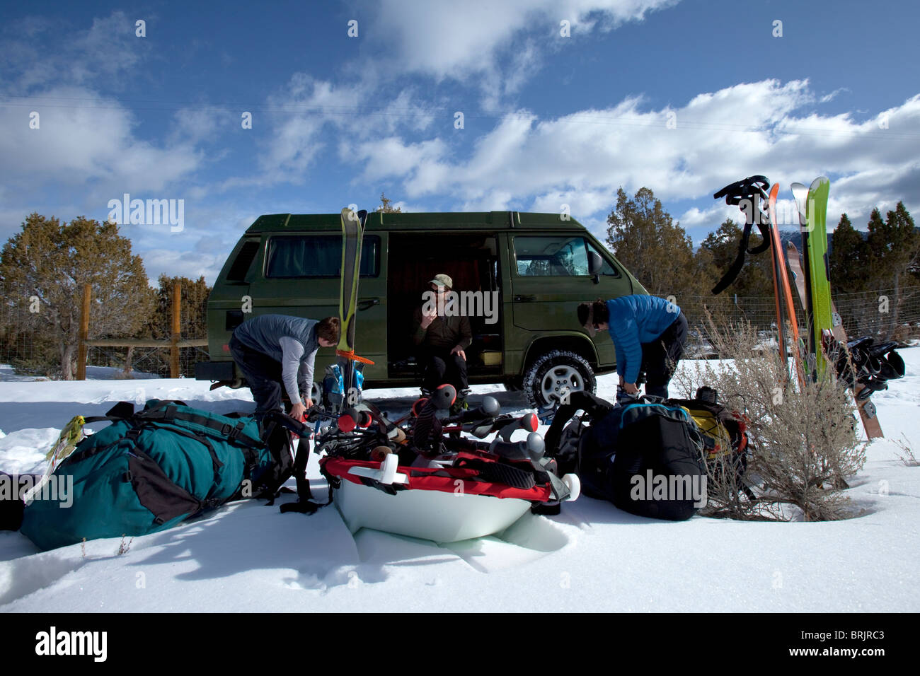 Three men getting ready for a ski trip next to a classic van parked in the snow. - Stock Image