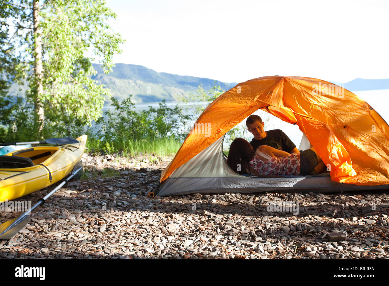 A young couple camping talk in their tent next to kayaks with lake in the background in Idaho. Stock Photo