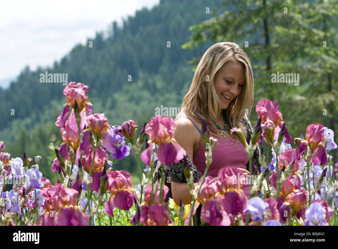 Girl stands in a field of flowers while smiling. - Stock Image