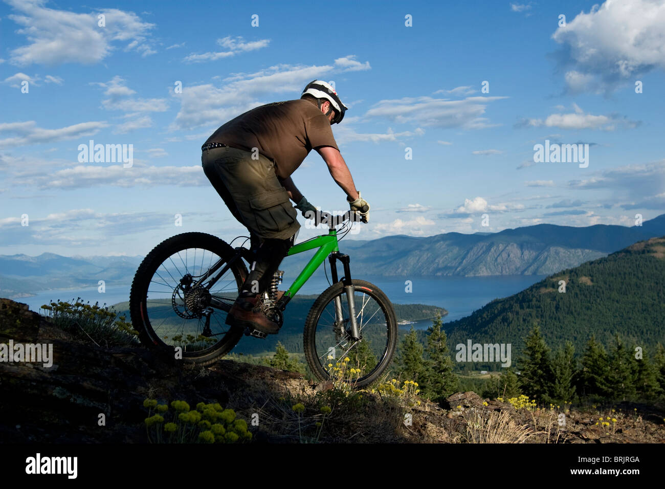 Young man mountain biking with lake in background. - Stock Image