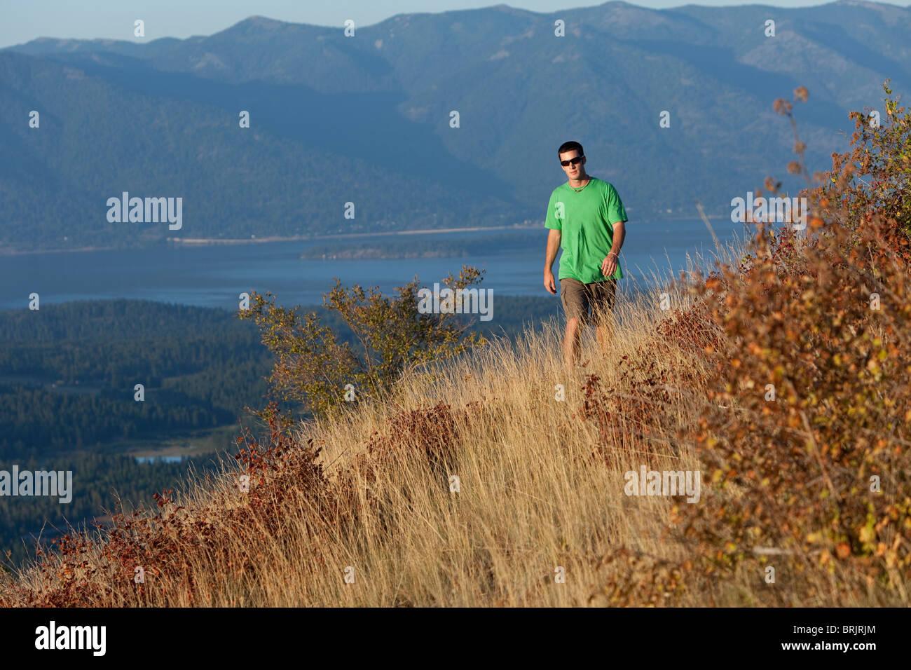 Young man hiking at sunset in Idaho. - Stock Image