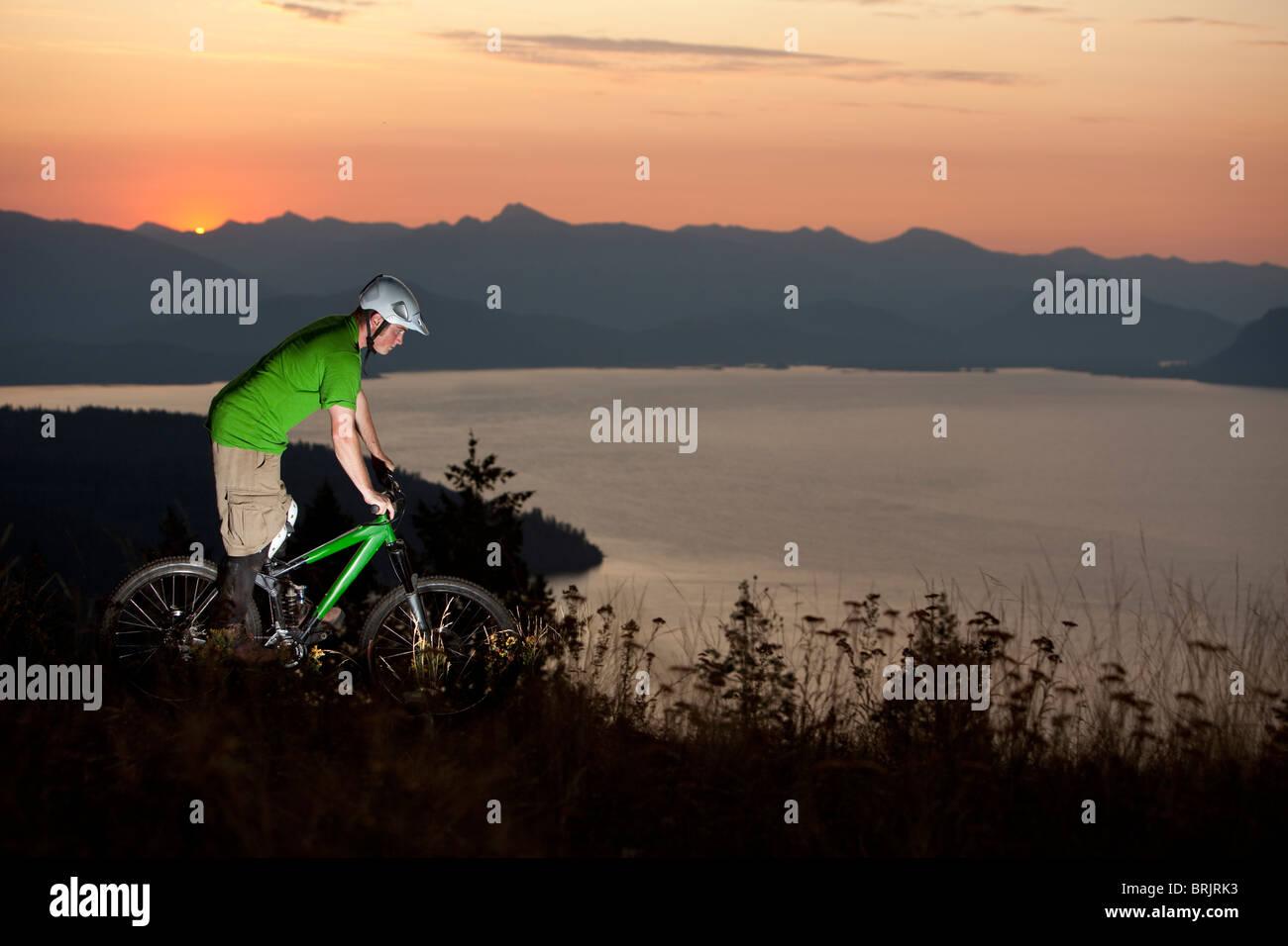 Young adult mountain biking at sunrise in Idaho. - Stock Image