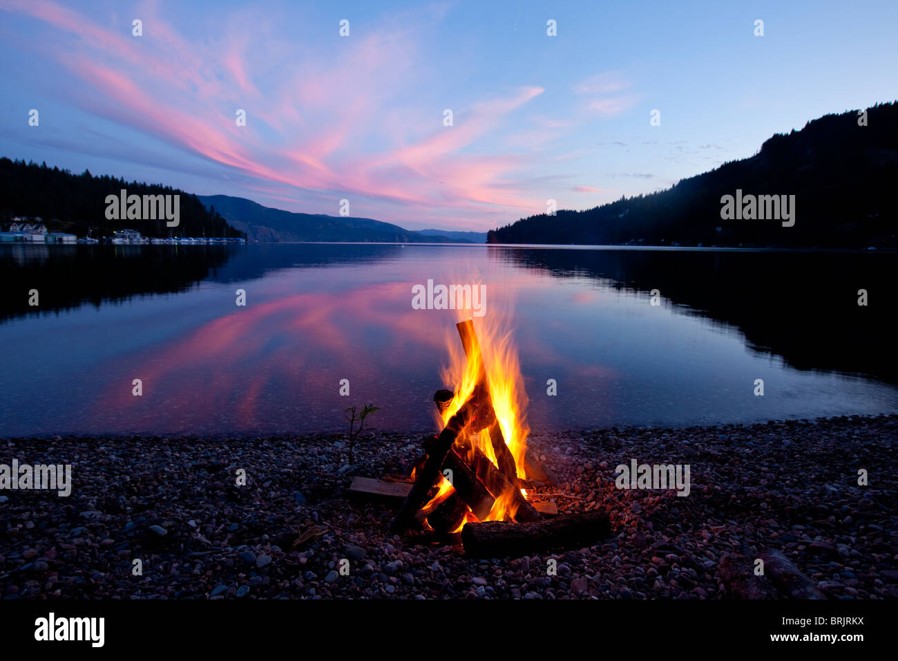 Campfire with sunset reflected on the lake in Idaho. - Stock Image