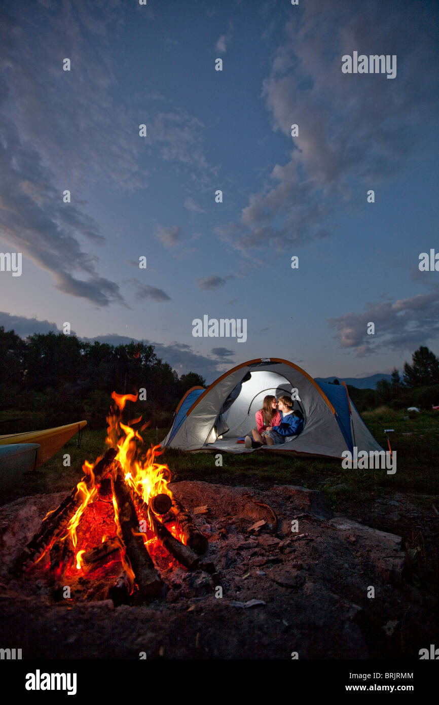 Young adult couple camping with a camp fire and kayaks on a beautiful summer evening. - Stock Image