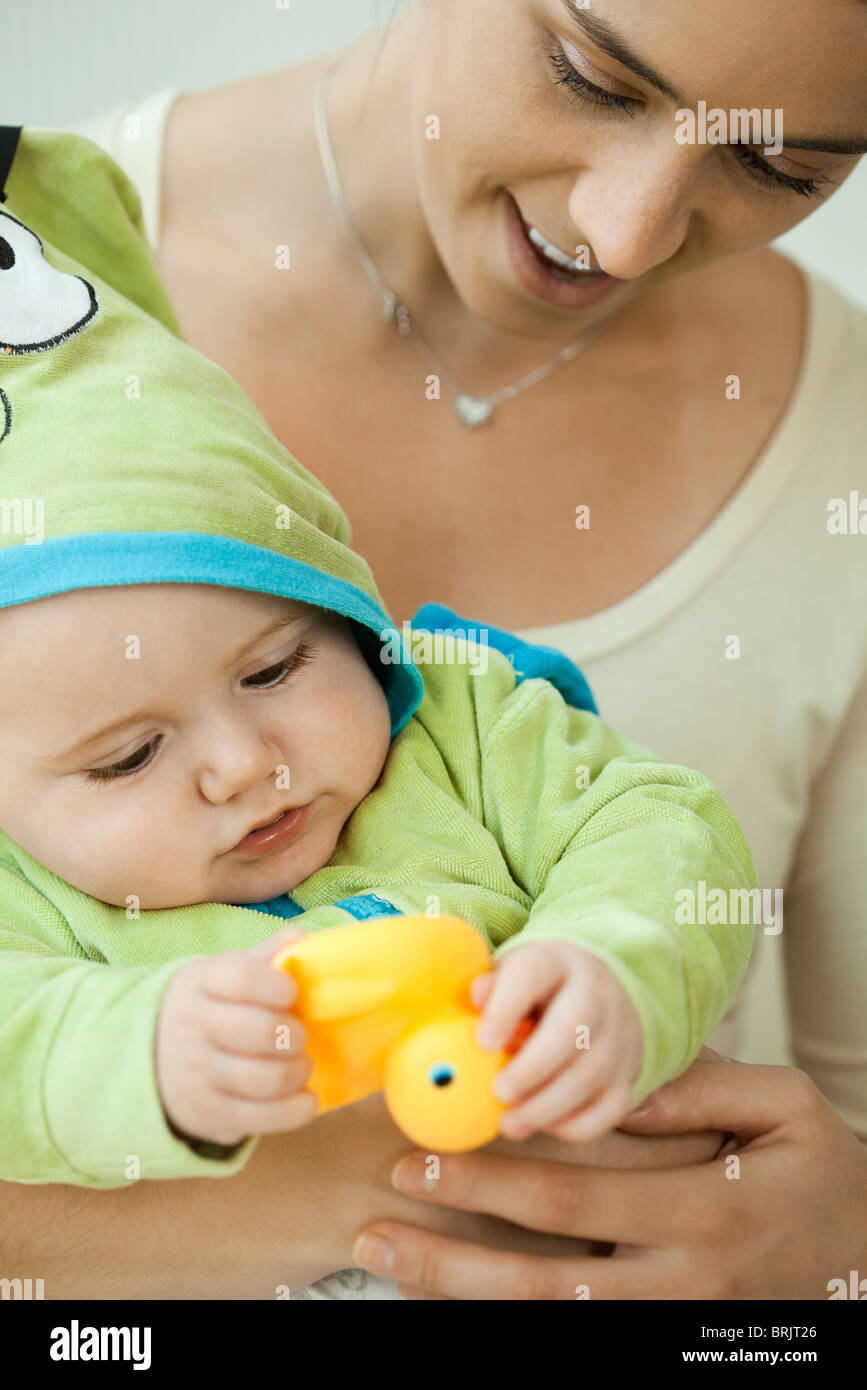 Mother and infant playing with rubber duck before bathtime - Stock Image