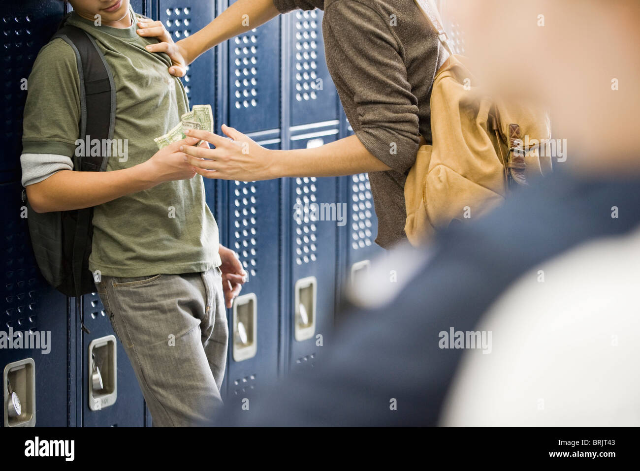 Teenage boy bullying classmate and stealing his money - Stock Image