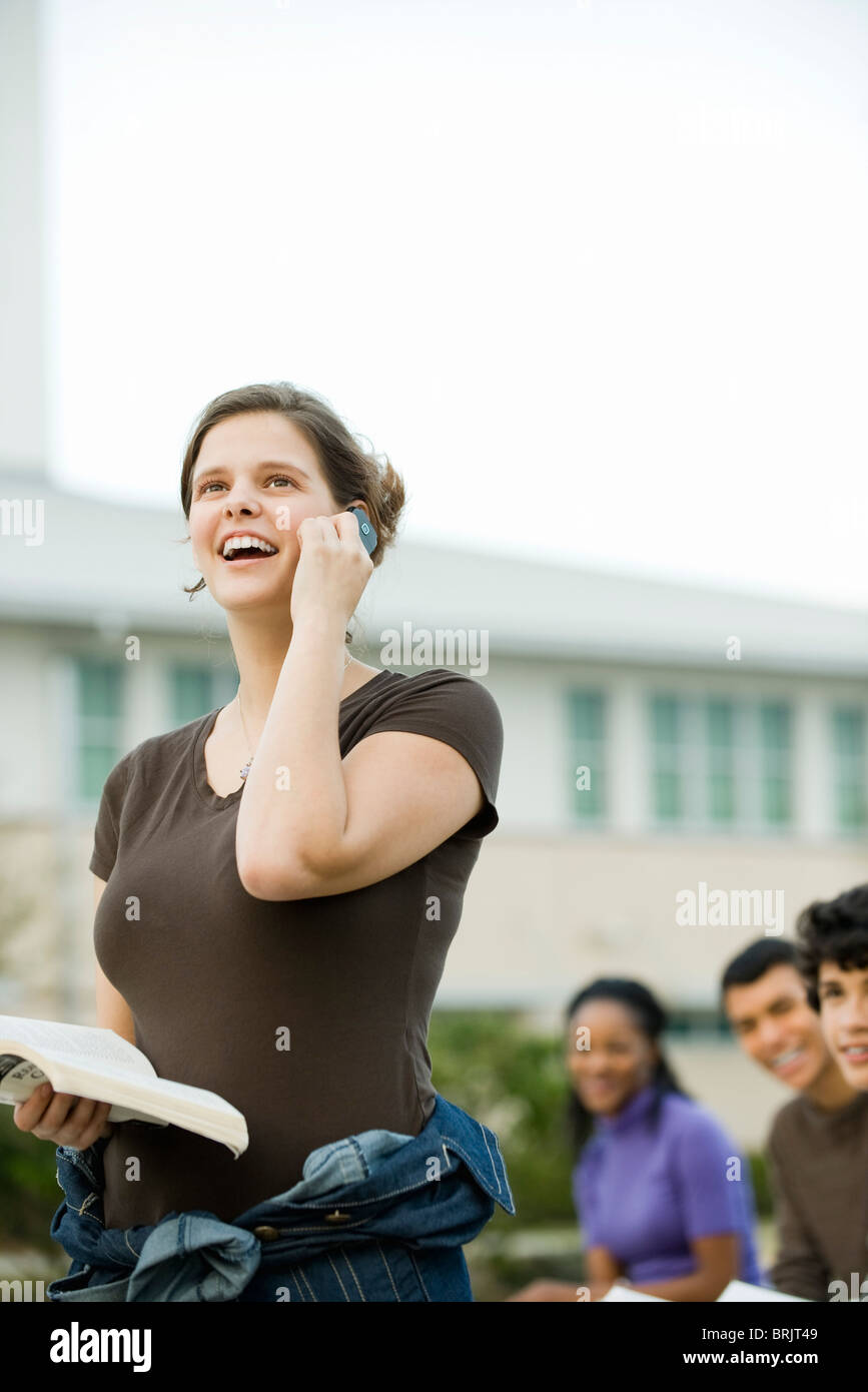 Young woman using cell phone, receiving good news - Stock Image