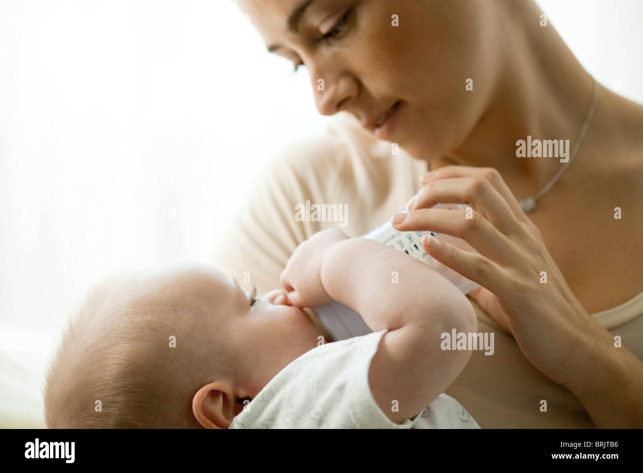 Mother feeding infant with baby bottle - Stock Image