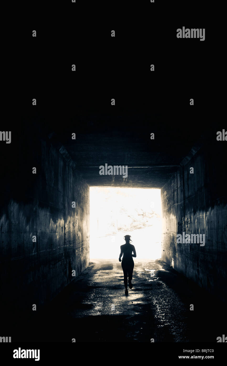 An athletic woman runs through a dark tunnel in Salt Lake City, UT. - Stock Image