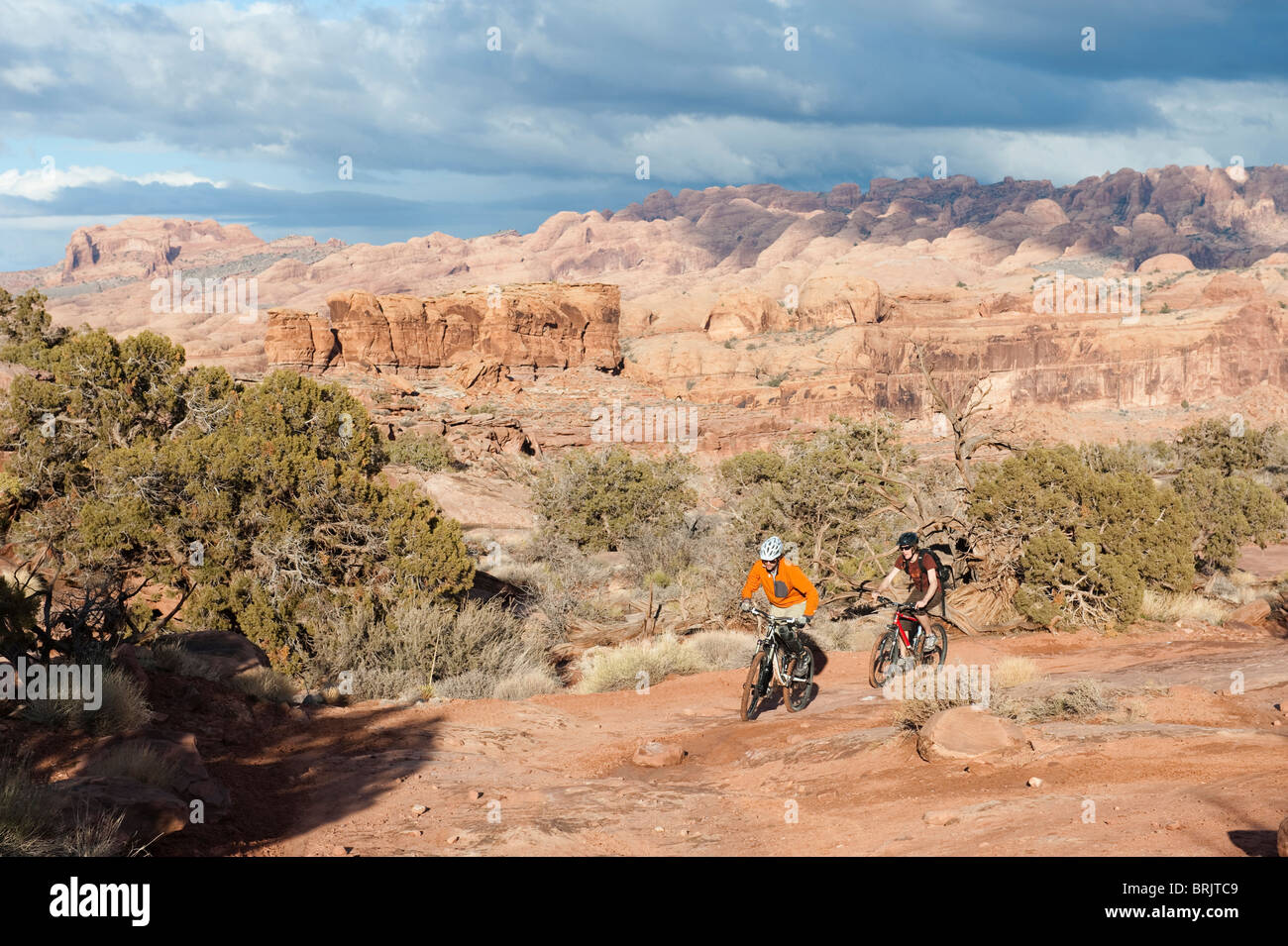 Two young men ride their bikes across the slickrock on the Amasa Back Trail in Moab, UT. - Stock Image