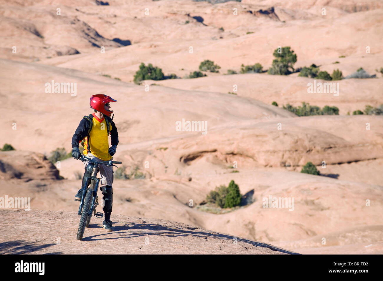 A mountain biker rests during a ride on the Slickrock Trail, Moab, UT. - Stock Image