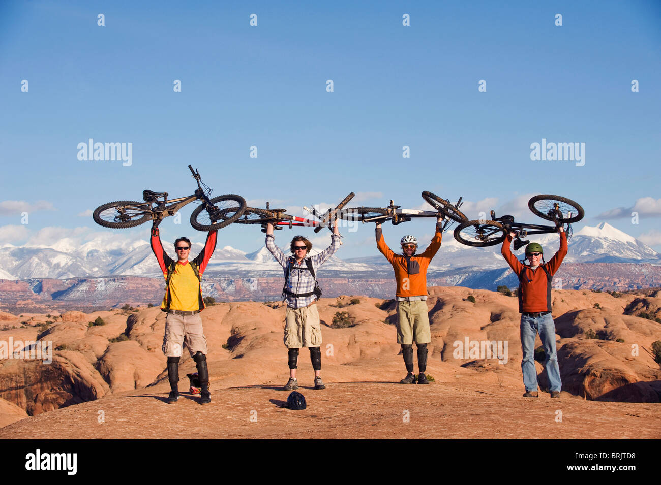Four young men hold their bikes above their heads on the Slickrock Trail, Moab, UT. - Stock Image