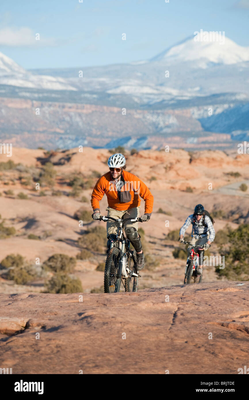 Two young men ride their mountain bikes on the Slickrock Trail, Moab, UT. Stock Photo