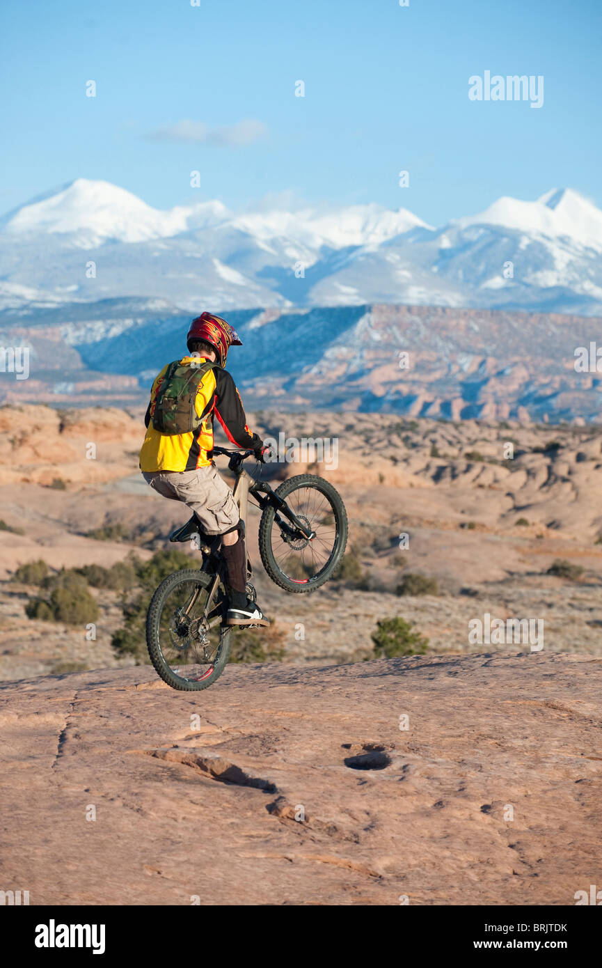 A young man rides a wheelie on the Slickrock Trail, Moab, UT. - Stock Image