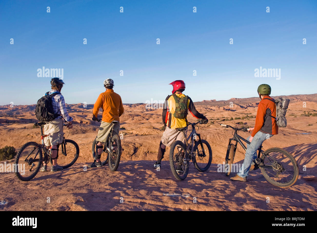Four young men enjoy the view during a mountain bike trip on the Slickrock Trail, Moab, UT. - Stock Image