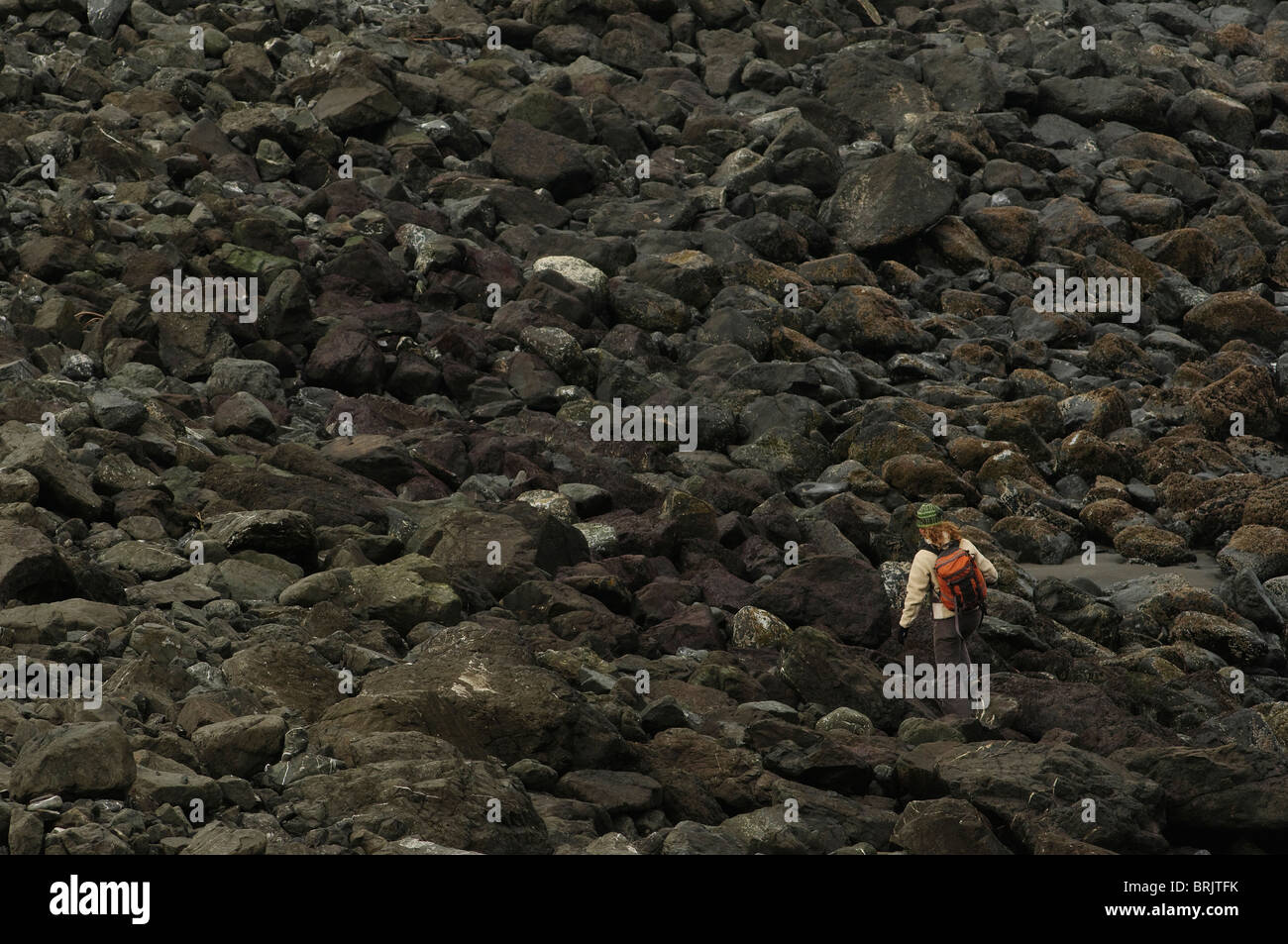A woman hikes on a beach on the Oregon Coast. - Stock Image