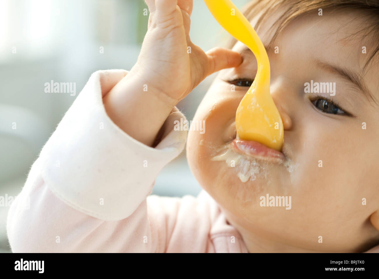 Infant eating with spoon - Stock Image