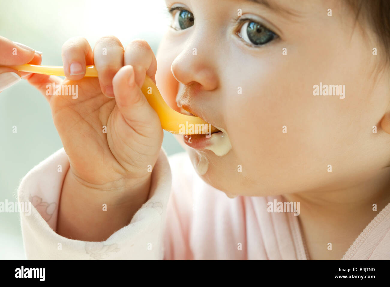 Infant learning to eat with a spoon - Stock Image