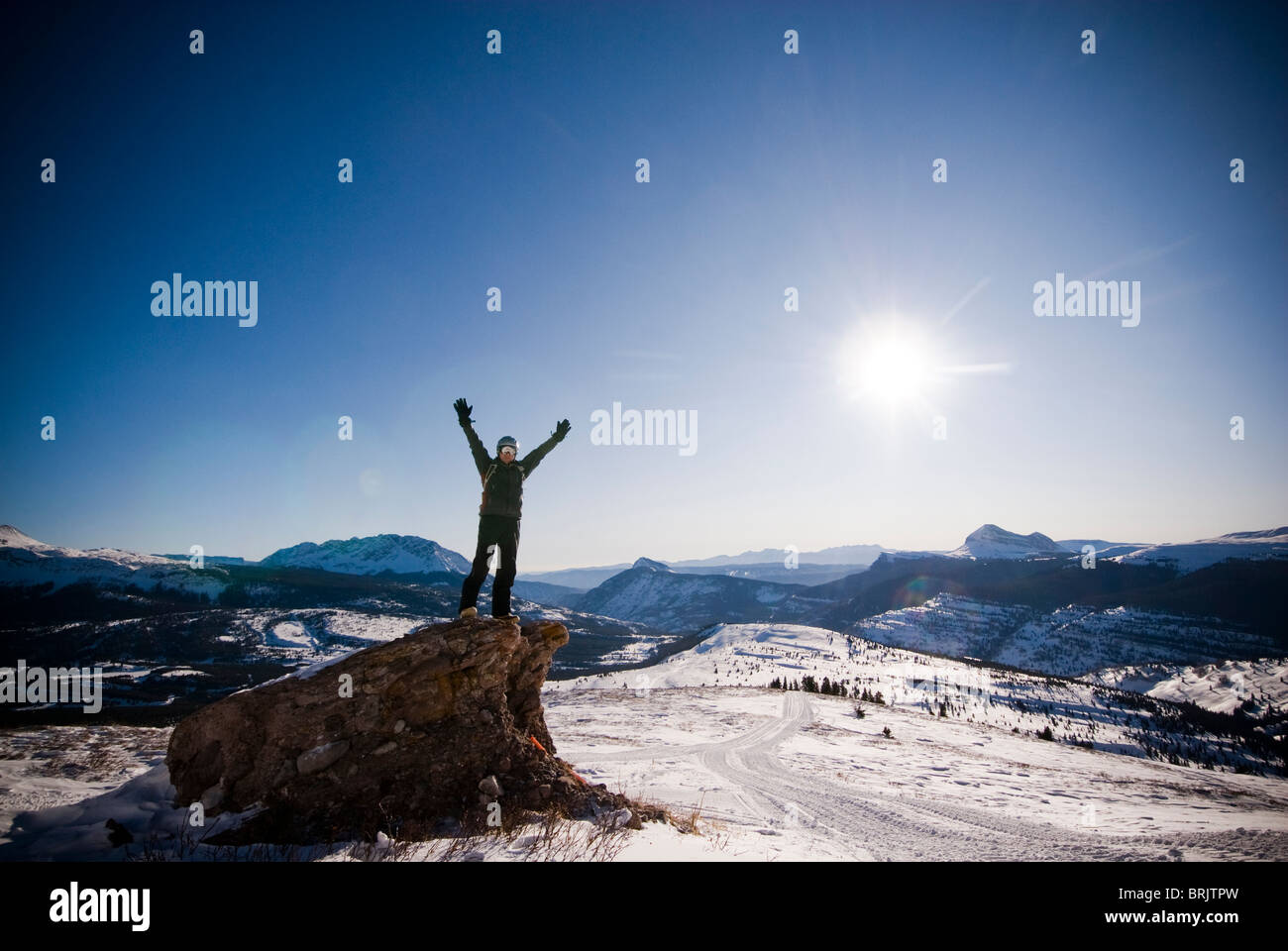 A middle aged man celebrates reaching a high point overlooking a snowy valley in the Rocky Mountains. - Stock Image