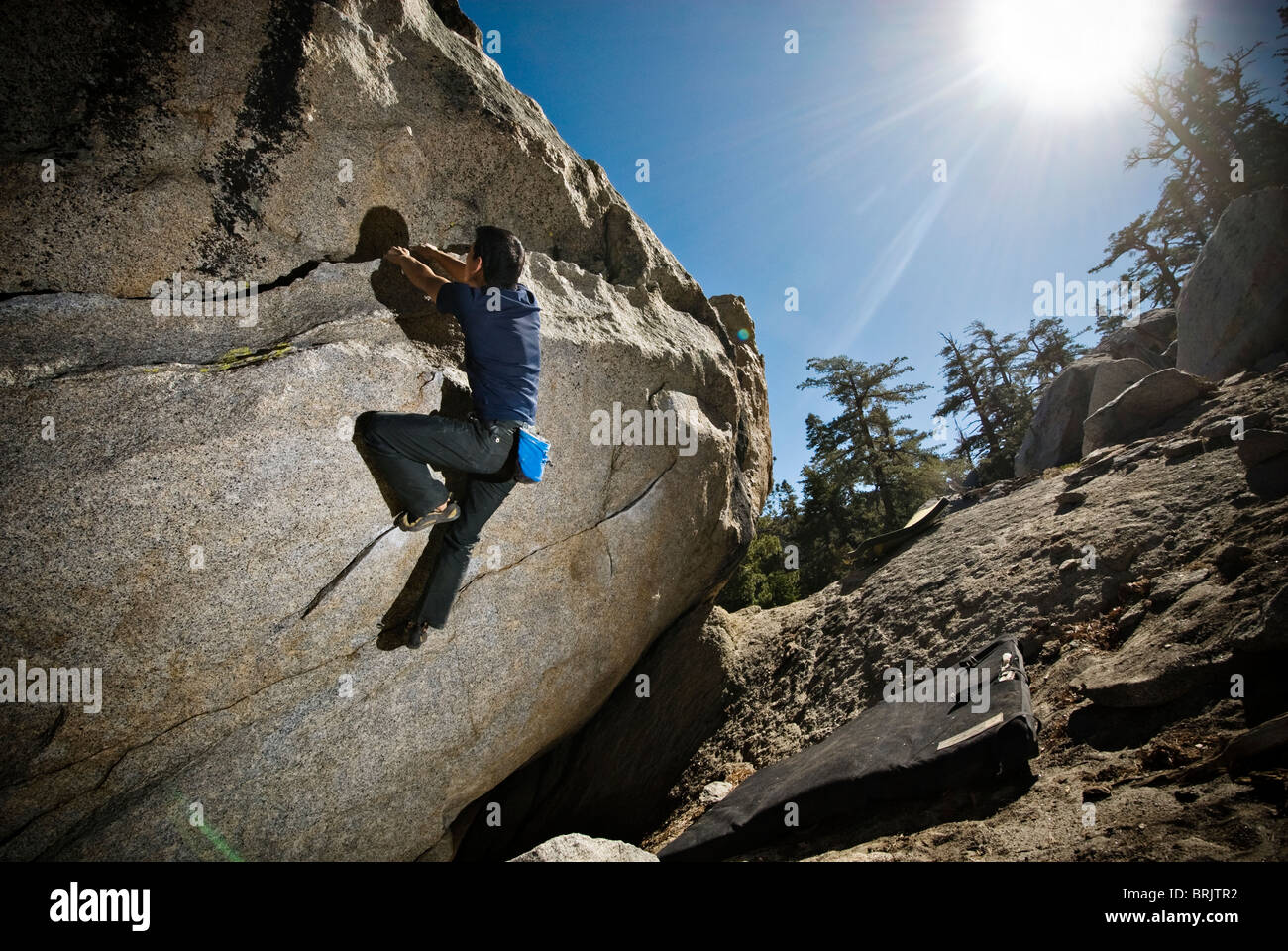 An Asian-American man rock climbs a boulder problem at The Tramway, Palm Springs, CA. - Stock Image