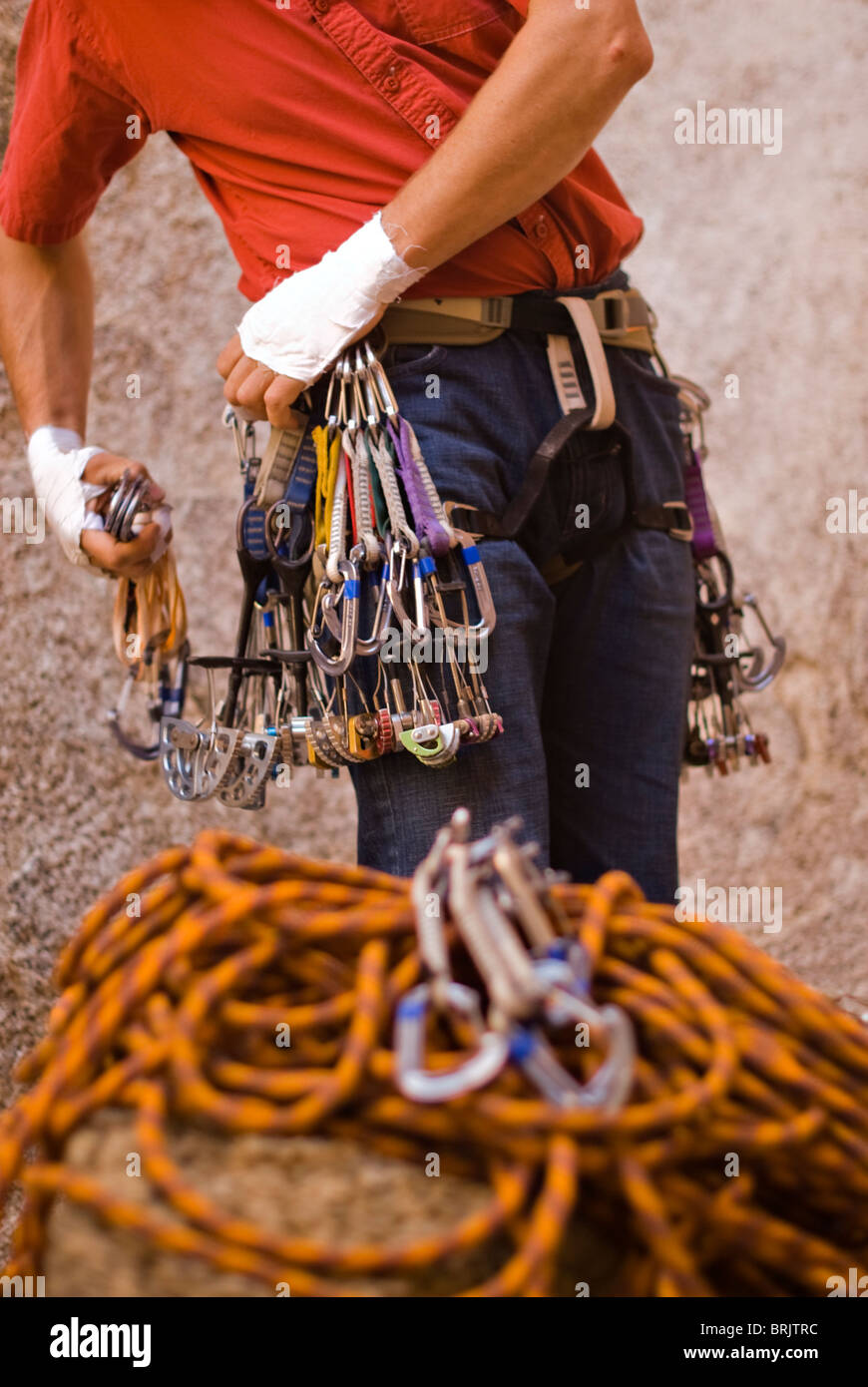 A climber in red prepares to lead climb Caught Inside, a route rated 5.10b. - Stock Image