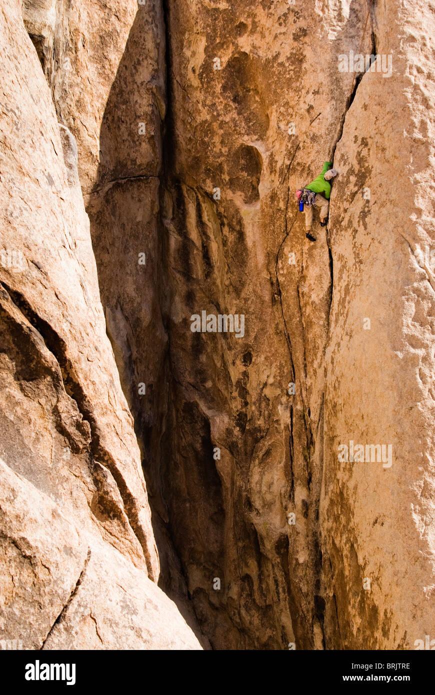 A young man climbing a long crack. - Stock Image