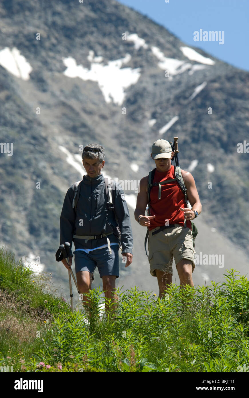 Two mountain guides discuss the upcoming schedule for a group of hikers in the Frnech Alps. - Stock Image