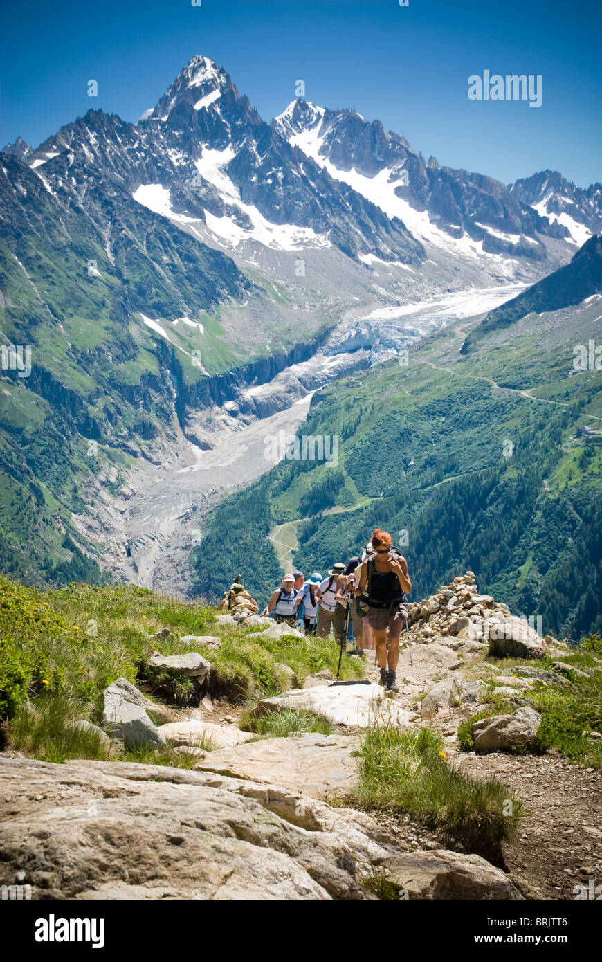 Hikers trek up a hill as the majesty of the Alps towers in the background. - Stock Image