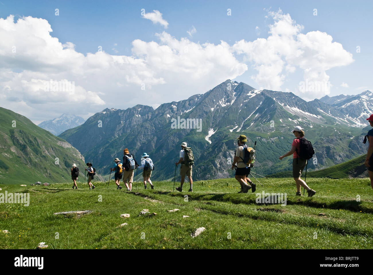 A group of hikers trek across a green mountainside on a partly cloudy day above Chamonix, France. - Stock Image