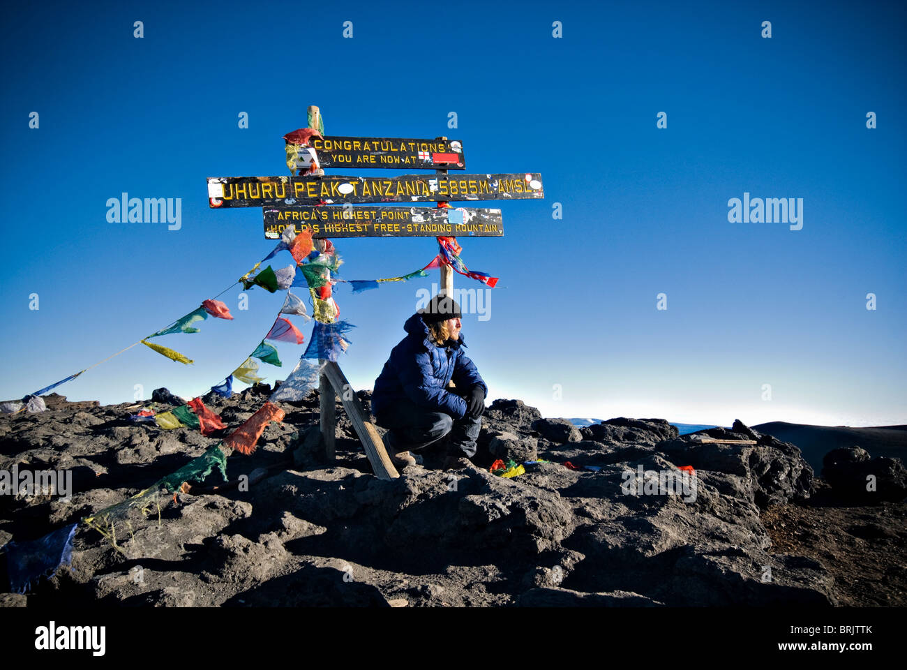 A young man reflects on the summit of Mt. Kilimanjaro, Tanzania, Africa as the sun rises. - Stock Image