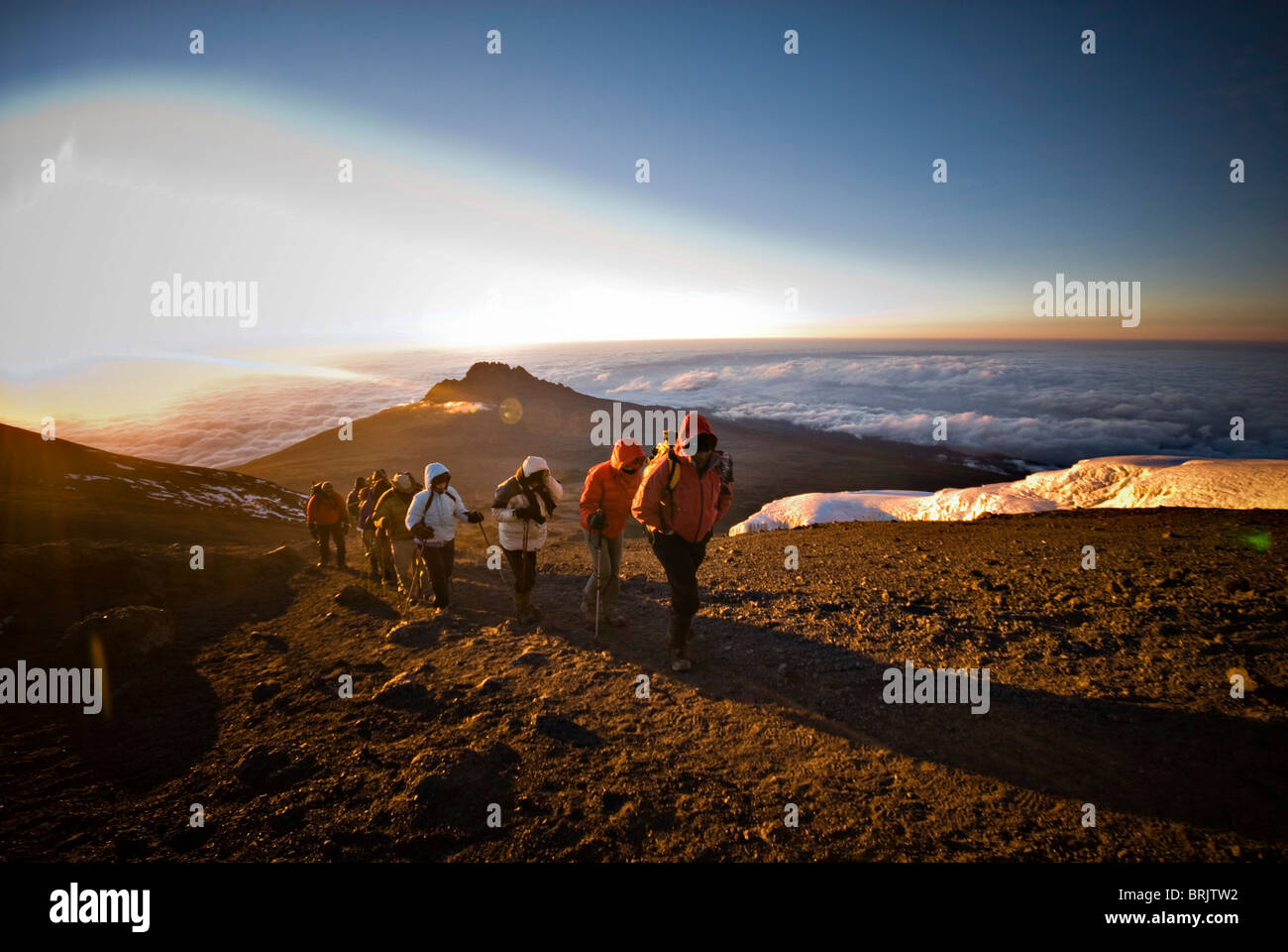 A team of hikers approach the summit of Mt. Kilimanjaro at sunrise after trekking six hours through the night. - Stock Image