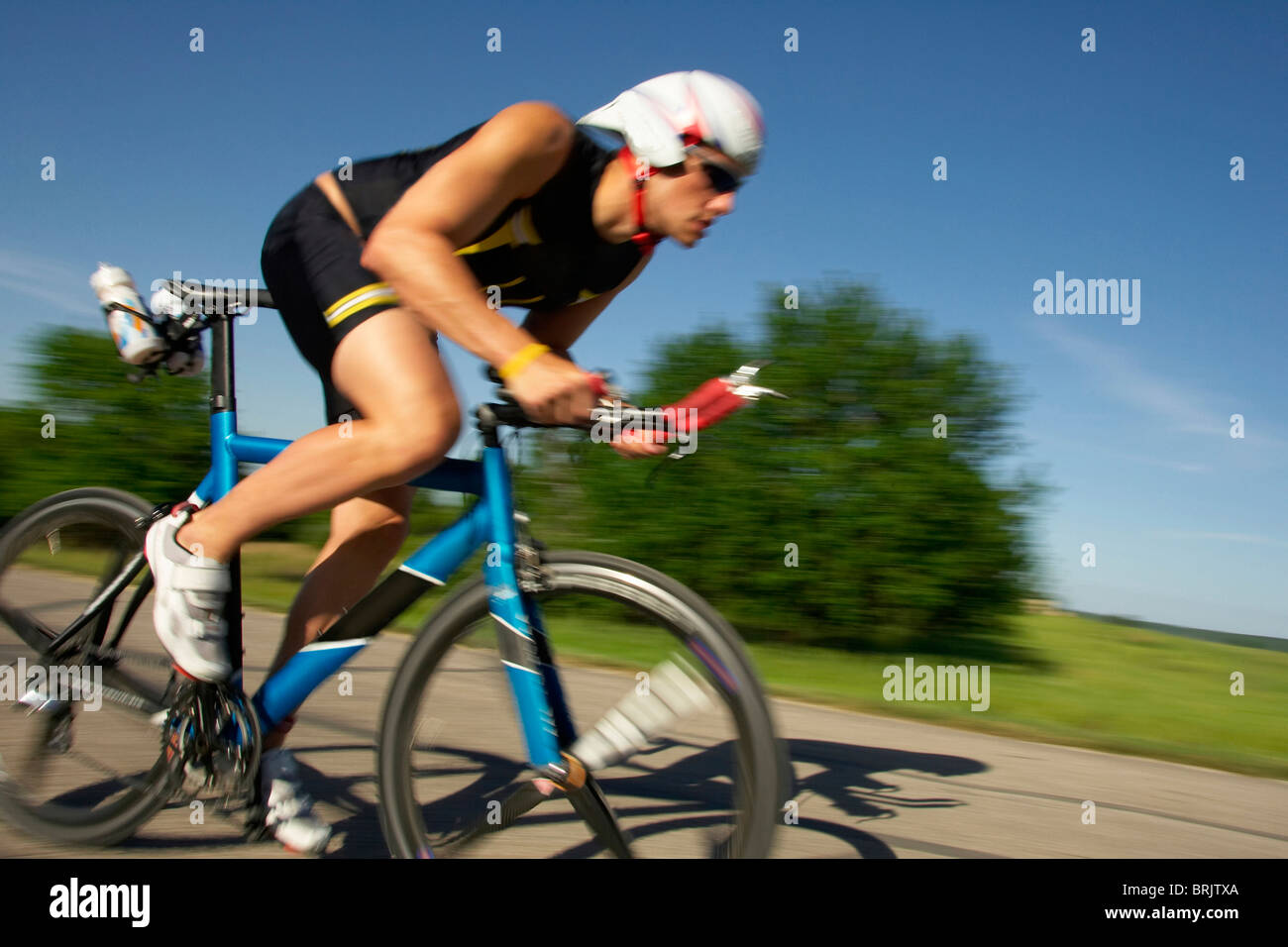 A male athelete training for a triathlon at a lake on a bike. - Stock Image