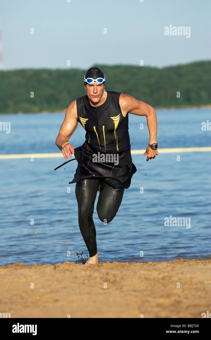 A male athelete running out of the water while training for a triathlon. - Stock Image