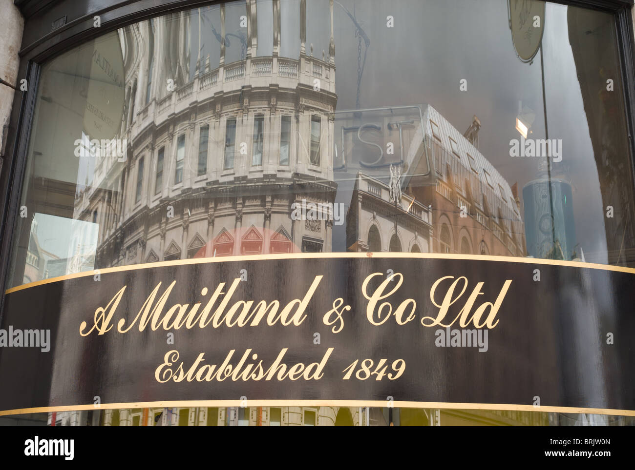 Building reflection in the store window of A. Maitland & Co, Picadilly Arcade in London, England. - Stock Image