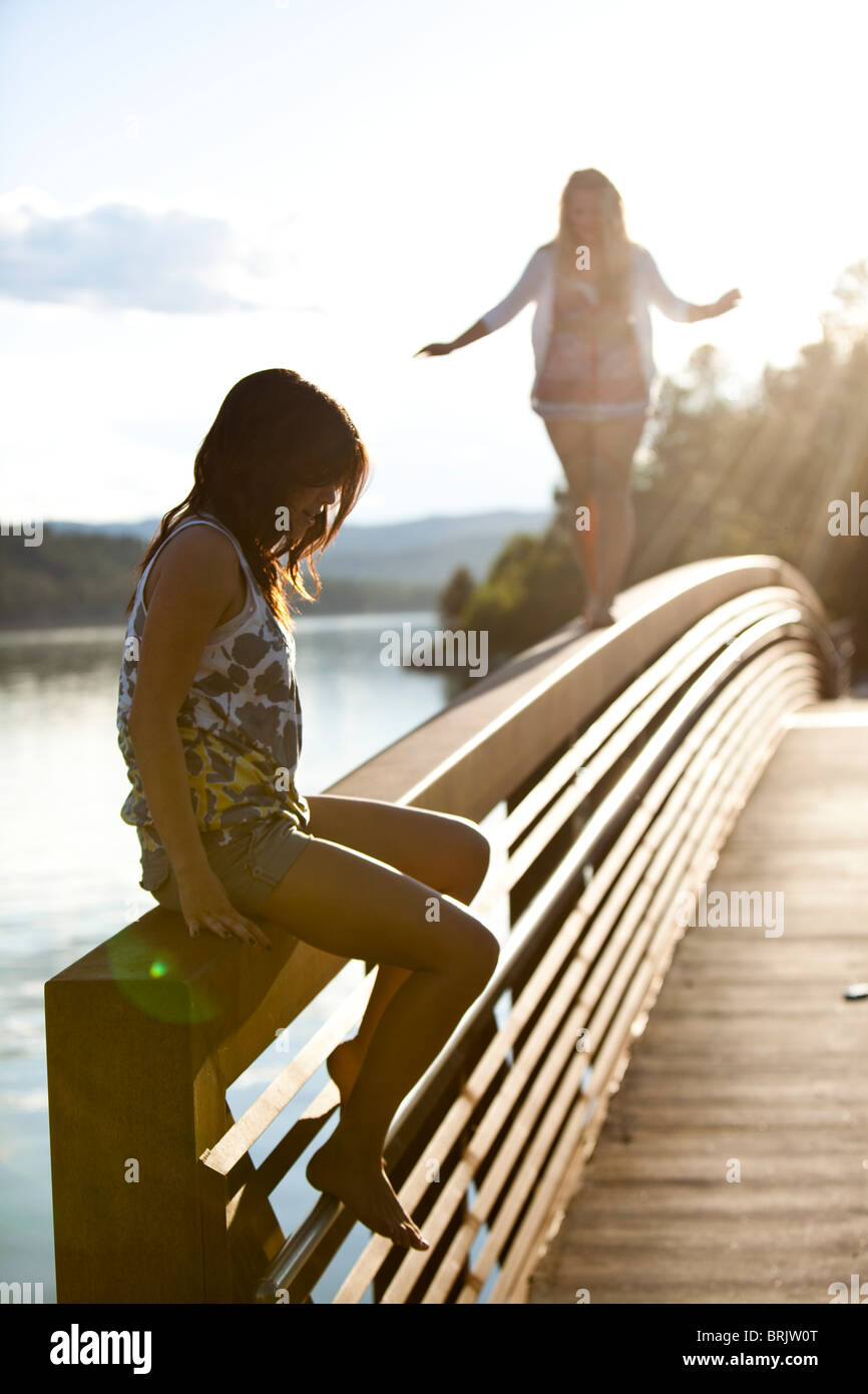 Two young women balance on a metal bridge in Idaho. - Stock Image