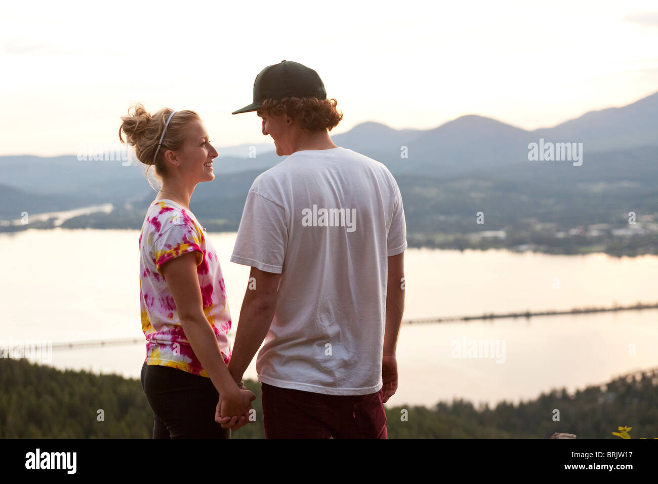A young adult couple hold hands and smile at sunset overlooking a large lake. - Stock Image