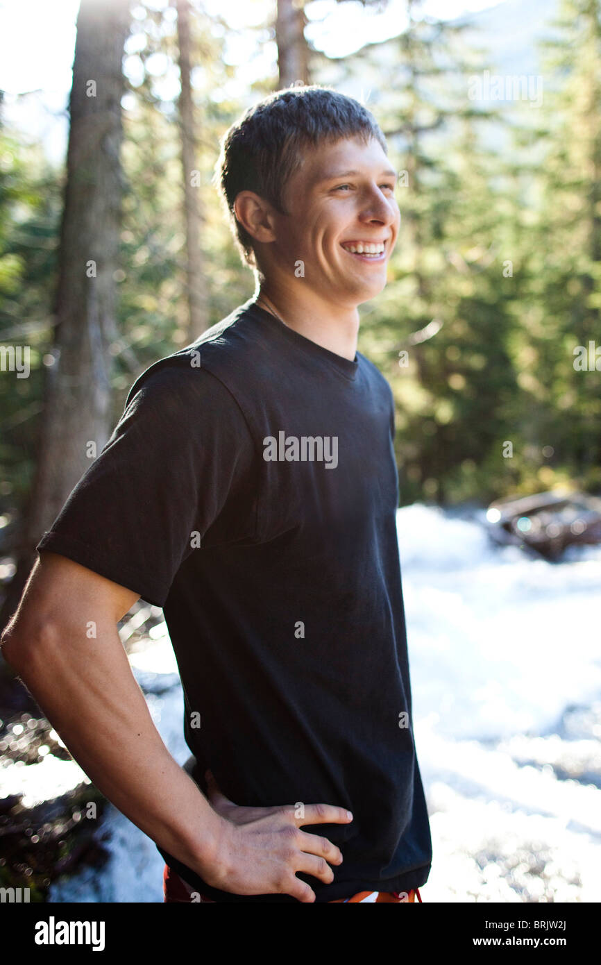 A young man smiles while standing next to a raging river in Idaho. - Stock Image