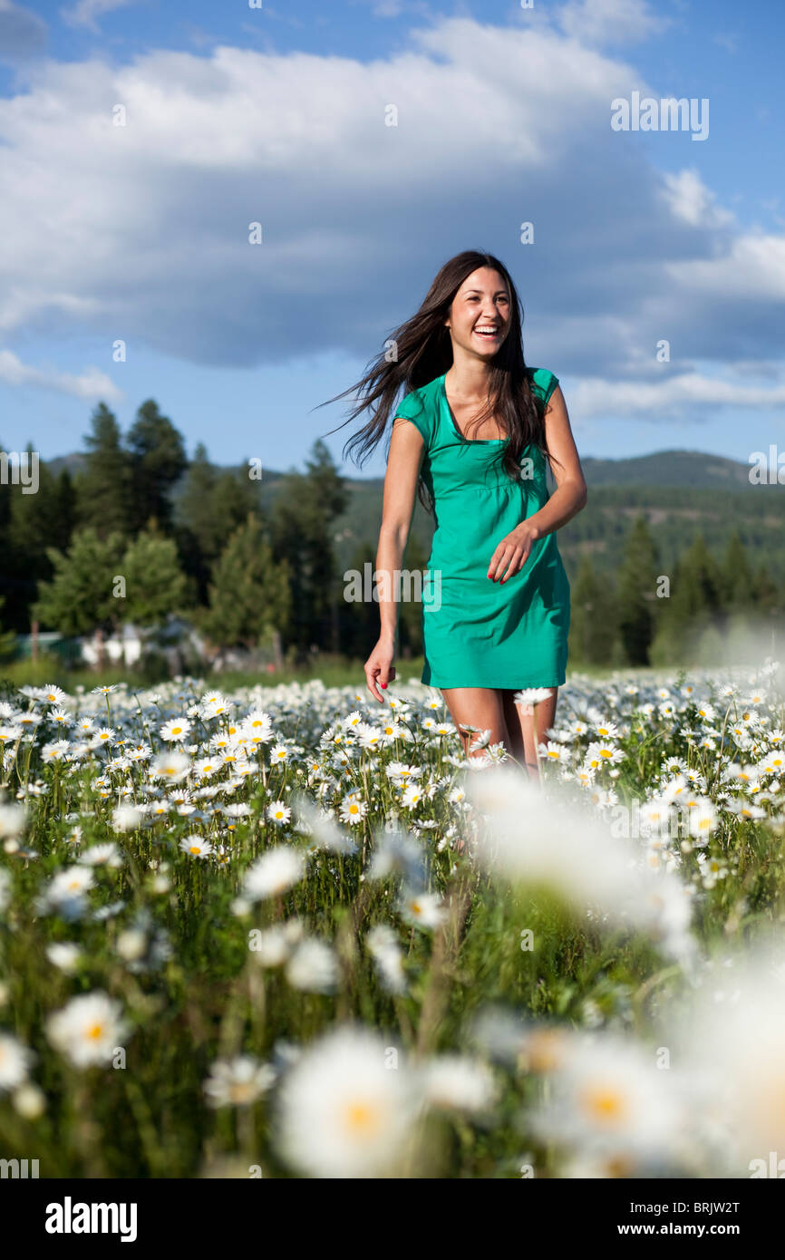 A young women laughs while dancing in a field of wild flowers. - Stock Image