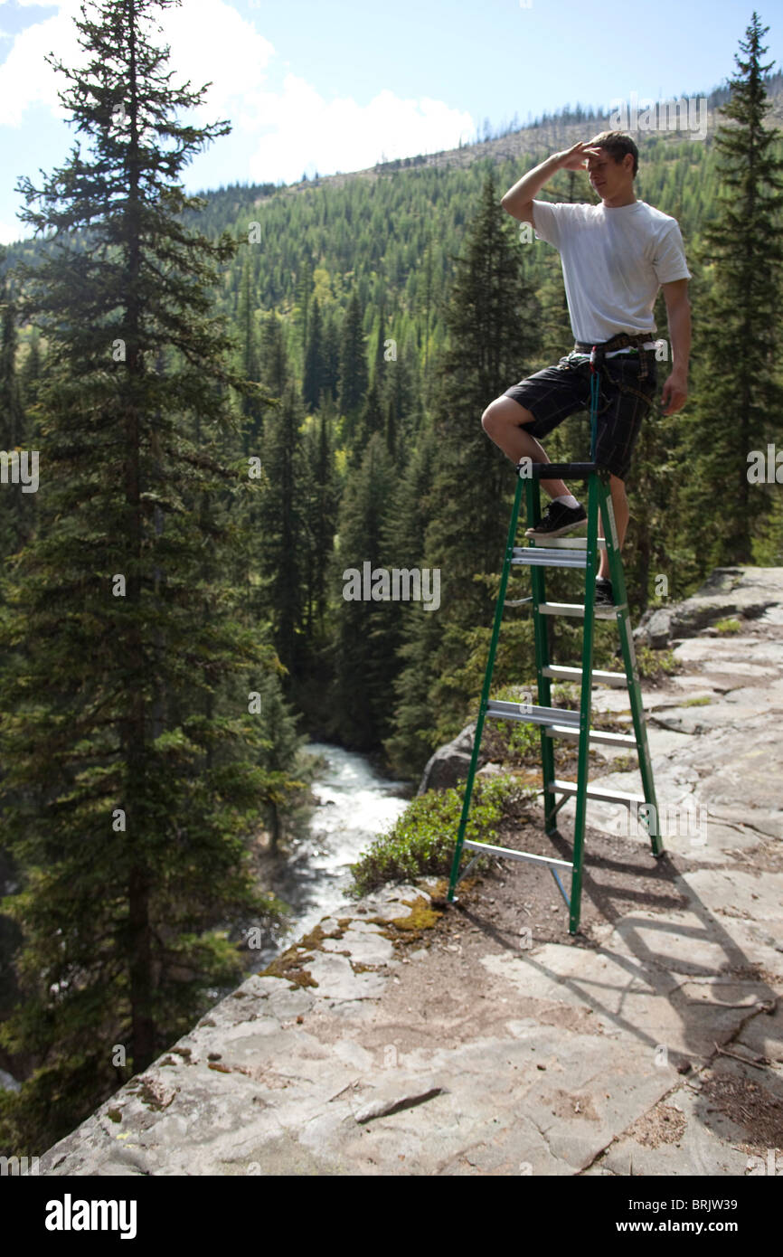 A young man stands on a ladder on the edge of a cliff surveying the surroundings. - Stock Image