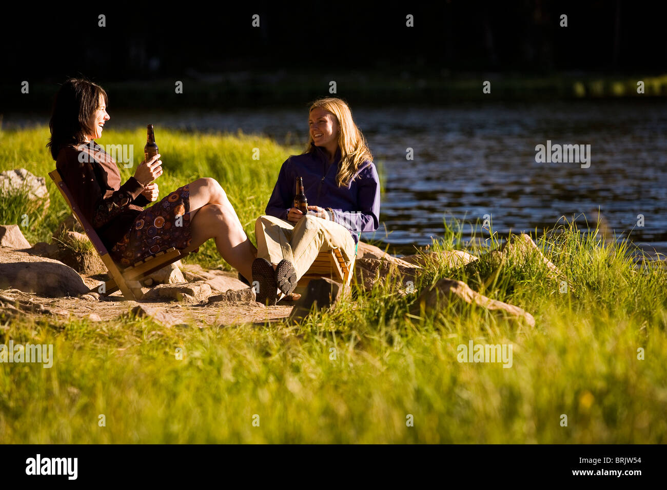 Two women enjoy one another's company and a beer on the shore of a mountain lake. - Stock Image