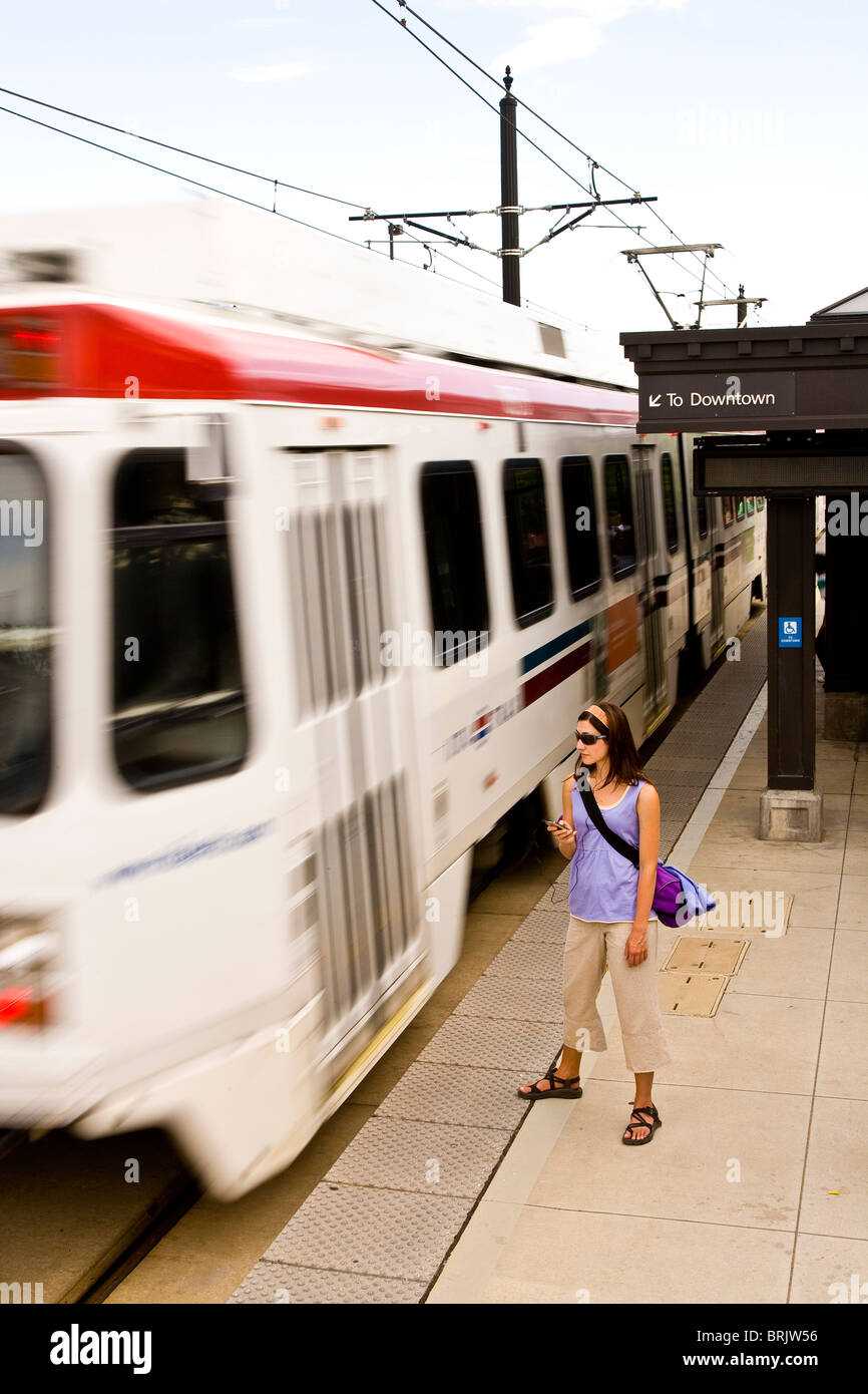 A young woman listens to her MP3 player while waiting for her train in Salt Lake City, Utah. - Stock Image