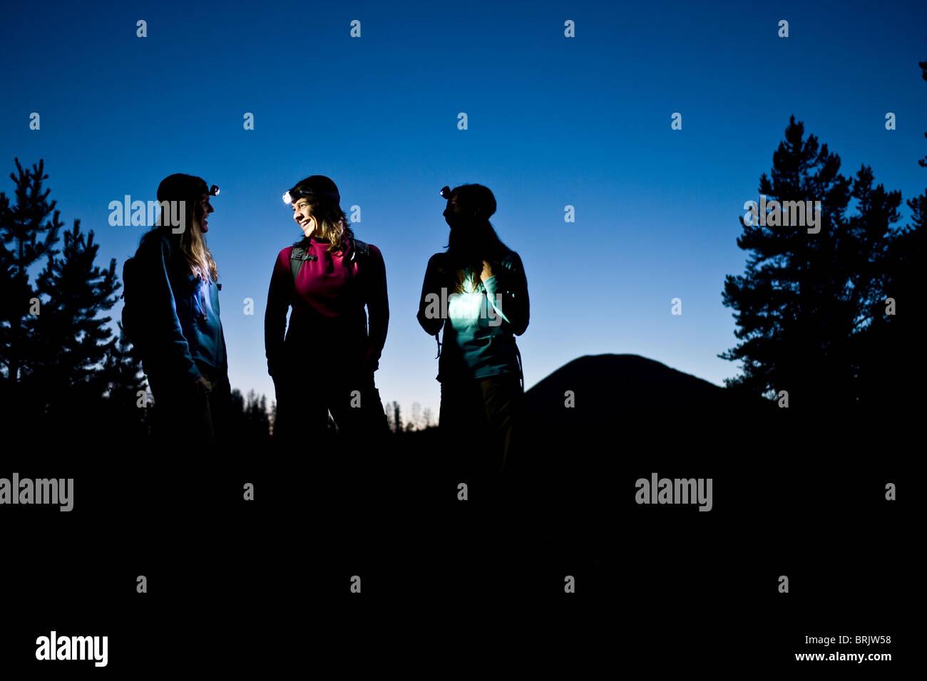 Three women talk while enjoying a twilight hike illuminated by headlamp. - Stock Image
