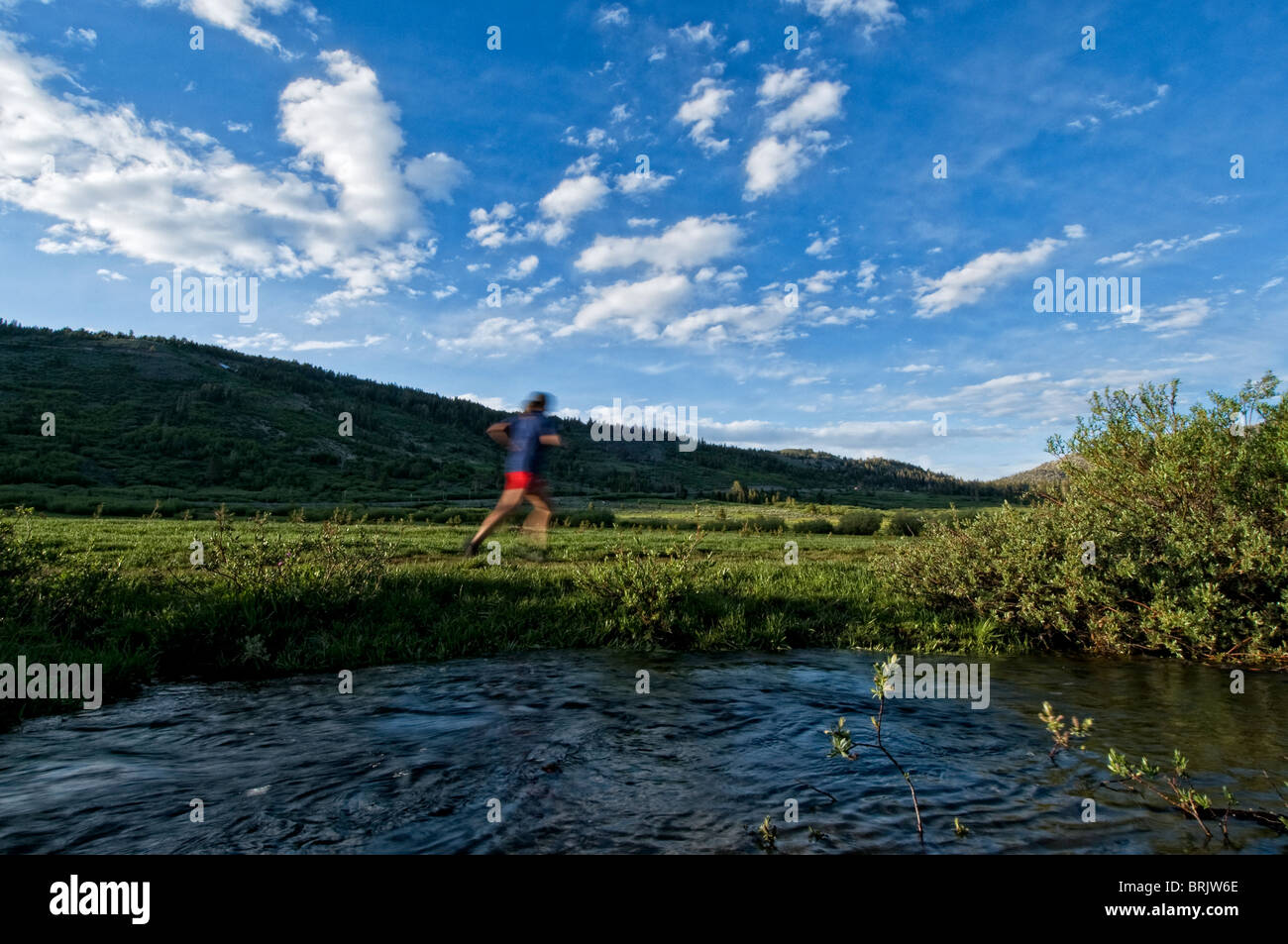 A young woman enjoys the evening light and empty trail during an evening trail run in Lake Tahoe, Nevada. - Stock Image