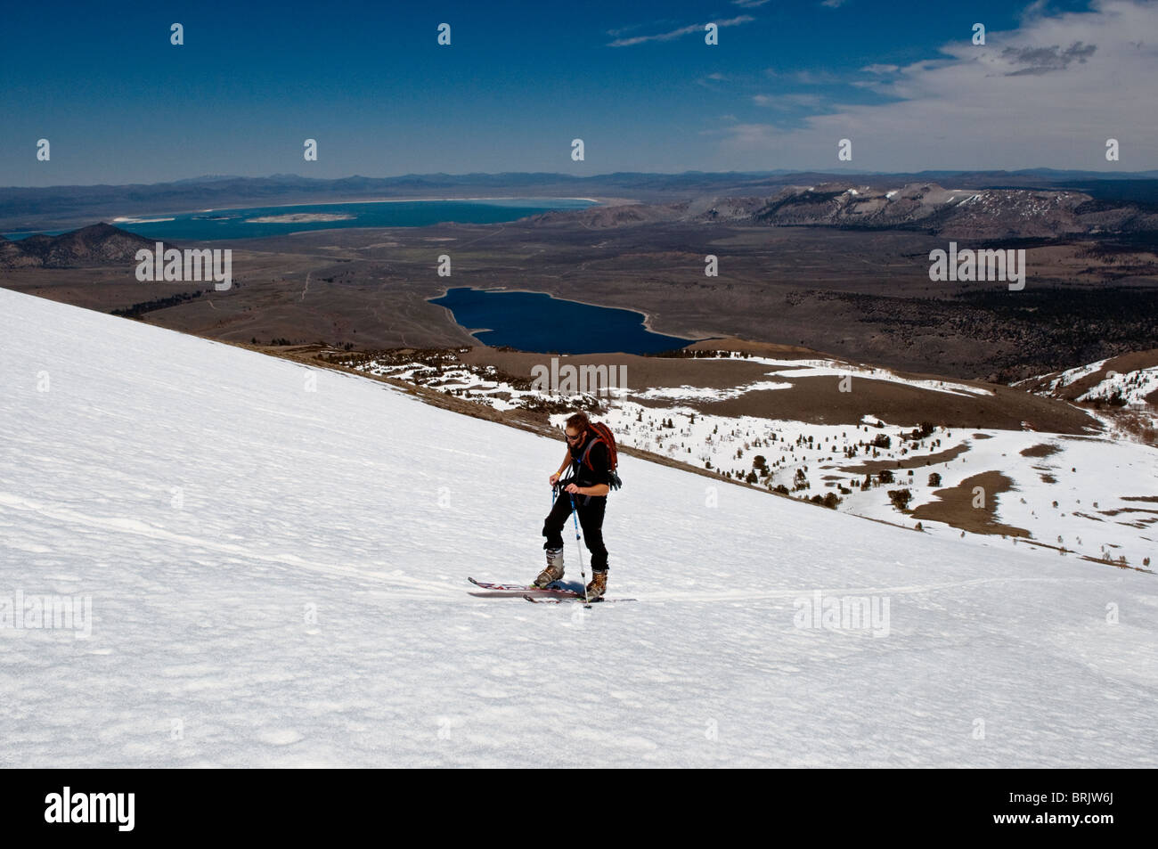 During his last ski tour for the season, a young man skins up the mountain with Mono Lake in the background, in - Stock Image