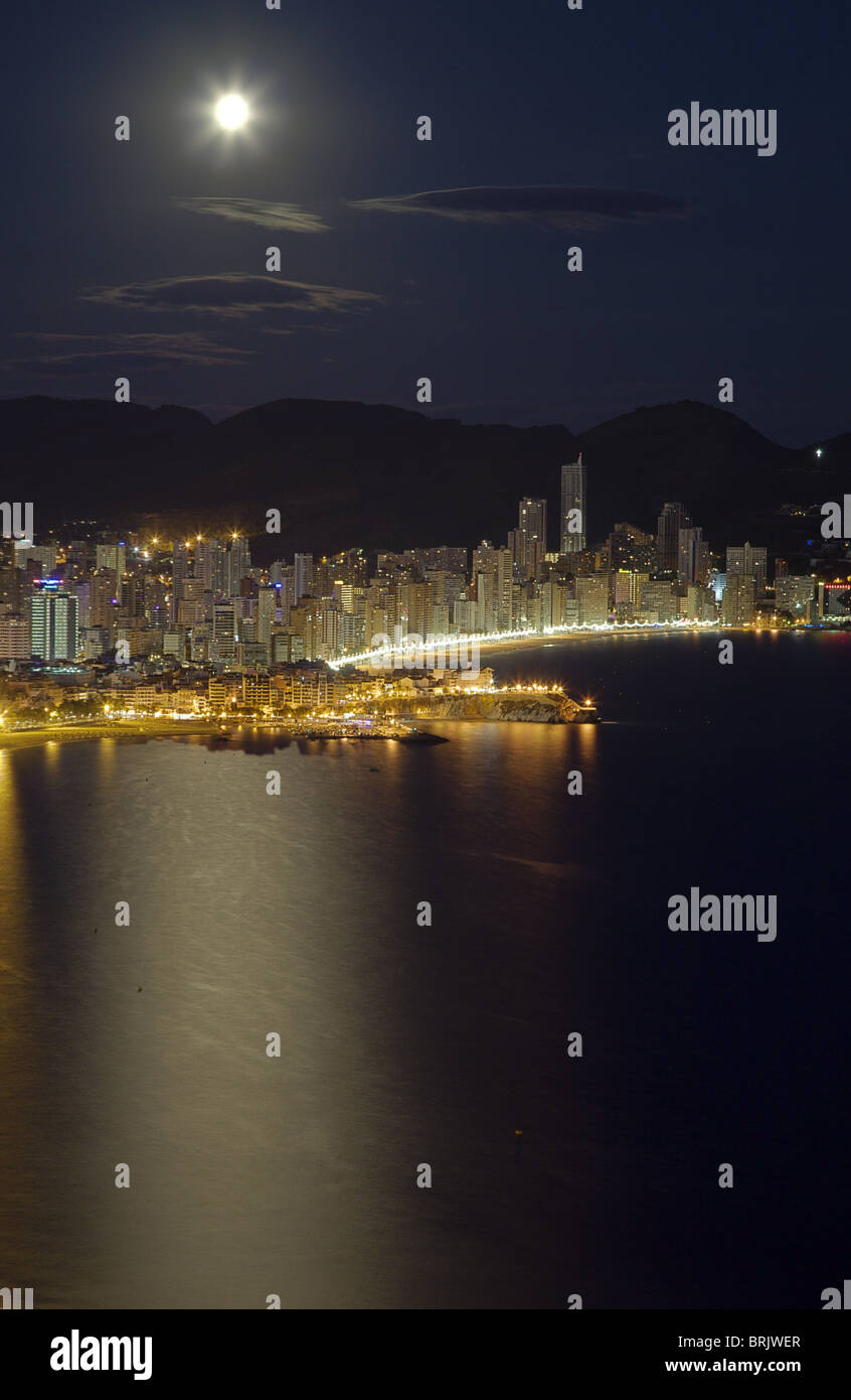 Benidorm's aerial vertical view at moon rise, with the castle, old town & beach illuminated. Foreground - Stock Image